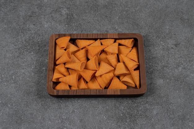Deliciosas batatas fritas crocantes na placa de madeira.