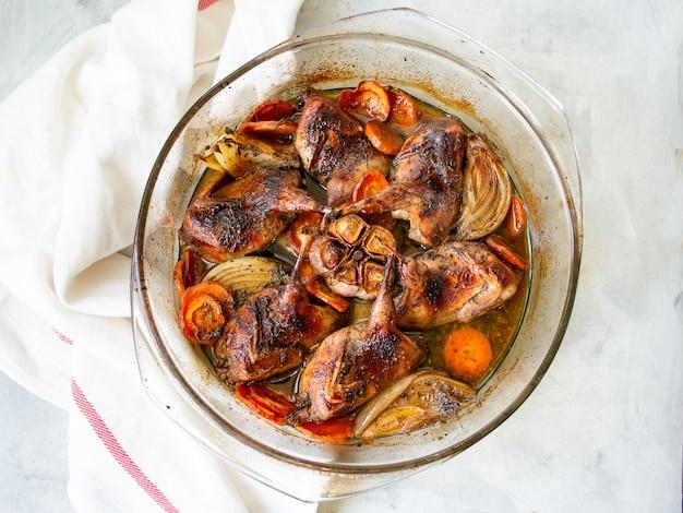 Deliciosas codornizes fritas com legumes - alho, cenoura, cebola, cozido em uma forma de vidro
