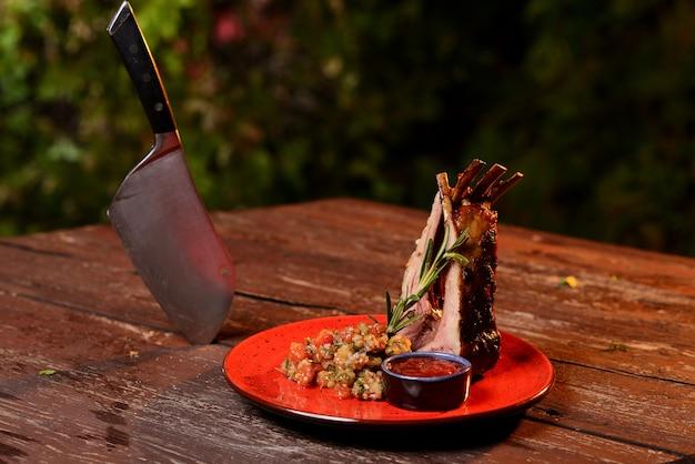 Deliciosas costelas grelhadas com molho. em uma placa vermelha em uma mesa de madeira