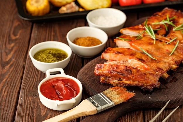 Deliciosas costelas grelhadas temperadas com um molho picante e servido com legumes frescos picados