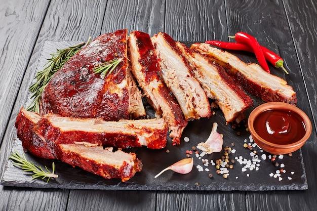 Deliciosas costelas suculentas de churrasco defumado caseiro de porco caem dos ossos em uma placa de pedra preta com especiarias
