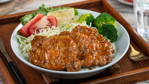 Deliciosas costeletas de porco suculentas com refeição de legumes em um prato na mesa de jantar.