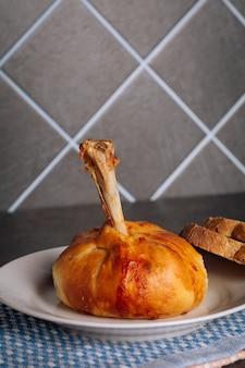 Deliciosas coxas de frango assadas em uma massa em um prato branco no fundo escuro