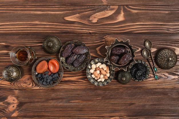 Deliciosas datas secas; nozes e chá na tigela metálica vintage turca no pano de fundo texturizado de madeira