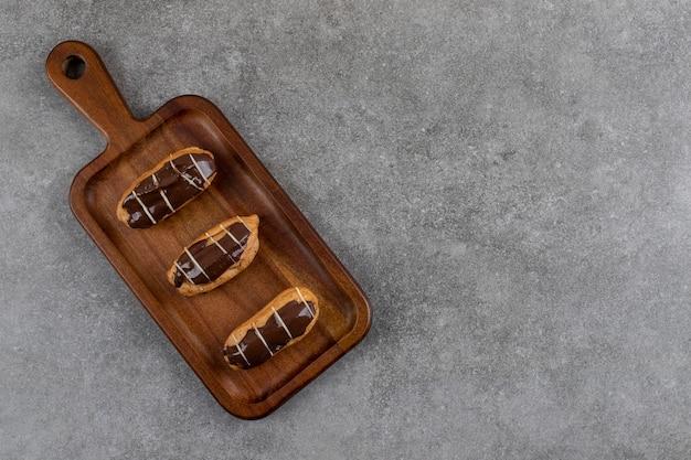 Deliciosas eclairs de chocolate em uma placa de madeira sobre uma superfície cinza
