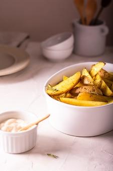 Deliciosas fatias de batata assada com alecrim e azeite em uma tigela de cerâmica