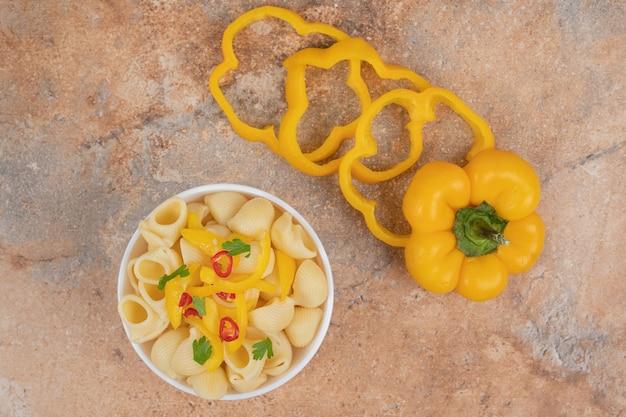 Deliciosas fatias de macarrão e pimenta em fundo laranja