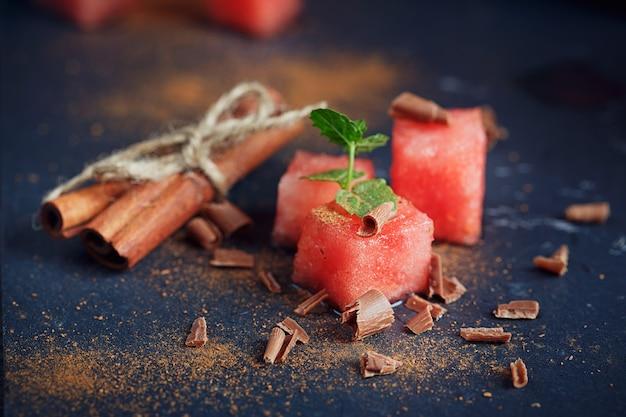 Deliciosas fatias frescas de melancia com canela e chocolate na superfície escura