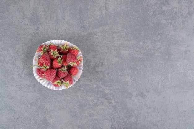 Deliciosas framboesas vermelhas em papel colorido. foto de alta qualidade