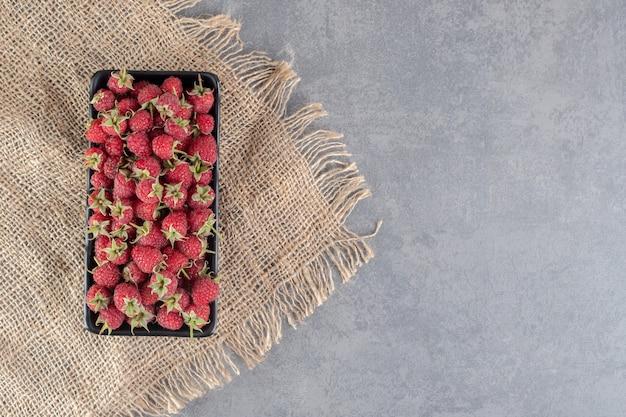 Deliciosas framboesas vermelhas na placa preta. foto de alta qualidade
