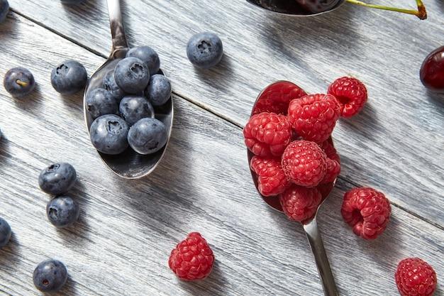 Deliciosas frutas doces em um fundo de madeira cinza de colher. postura plana. conceito de alimentação vegetariana.