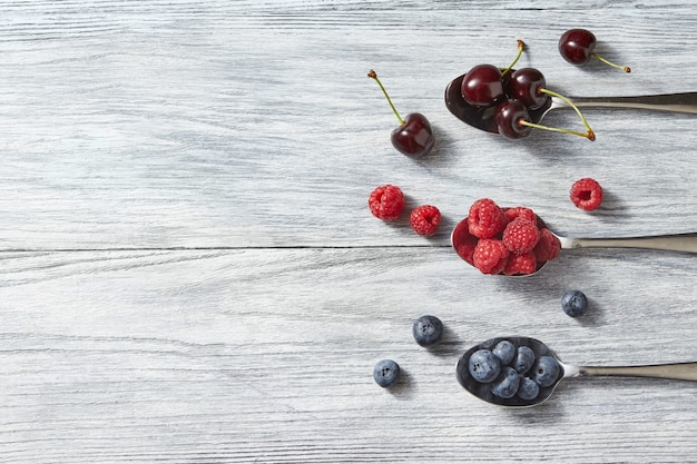 Deliciosas frutas doces em uma colher no fundo cinza de madeira. postura plana. conceito de alimentos orgânicos saudáveis com espaço de cópia. postura plana.