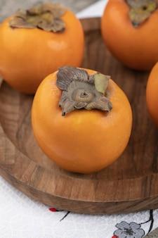 Deliciosas frutas maduras de caqui colocadas em um prato de madeira