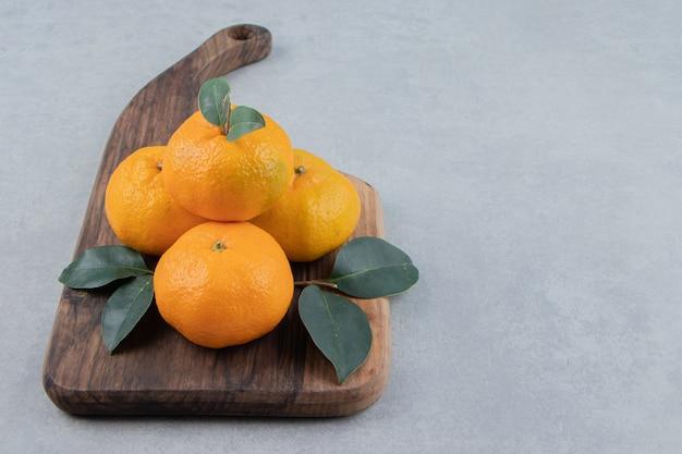 Deliciosas frutas tangerina em tábua de madeira