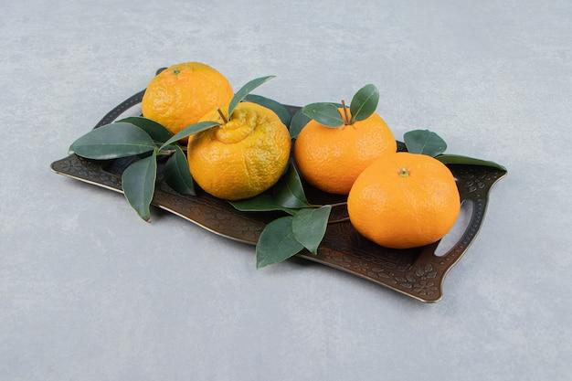 Deliciosas frutas tangerina na bandeja de metal.