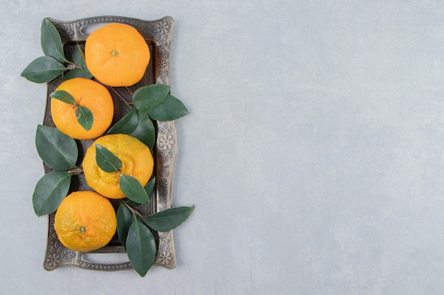 Deliciosas frutas tangerina na bandeja de metal