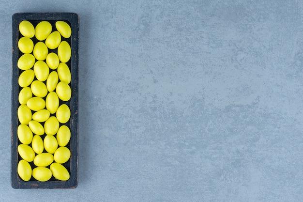 Deliciosas gomas na bandeja de madeira, sobre a mesa de mármore.