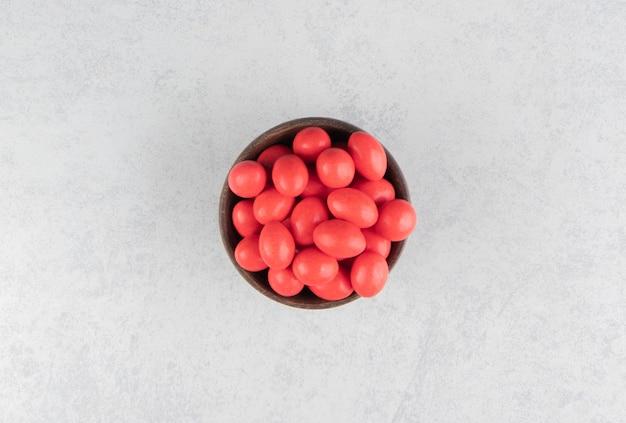 Deliciosas gomas vermelhas na tigela sobre a superfície de mármore