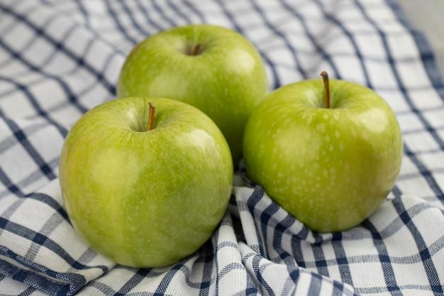 Deliciosas maçãs verdes frescas colocadas na toalha de mesa listrada.