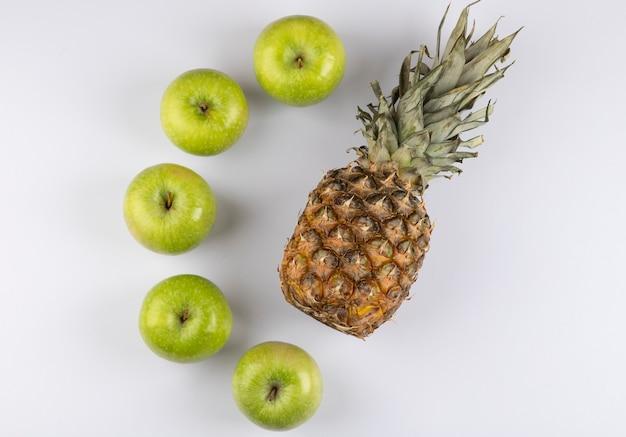 Deliciosas maçãs verdes frescas e abacaxi em branco.