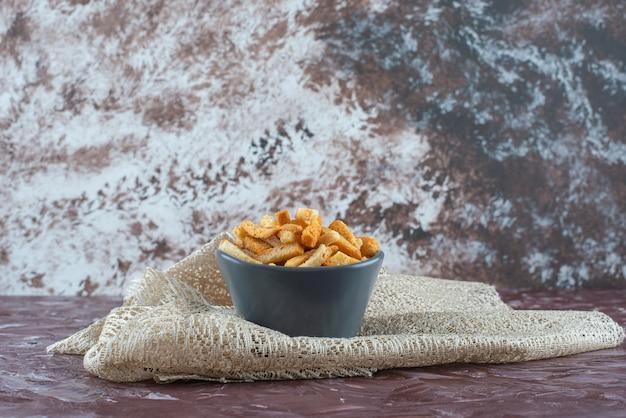 Deliciosas migalhas de pão crocantes em uma tigela na toalha de mesa em mármore.