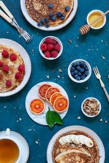 Deliciosas panquecas caseiras com framboesas, mirtilos, mel, nozes e frutas alaranjadas