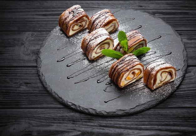 Deliciosas panquecas com cobertura de chocolate, caramelo e hortelã no fundo de madeira