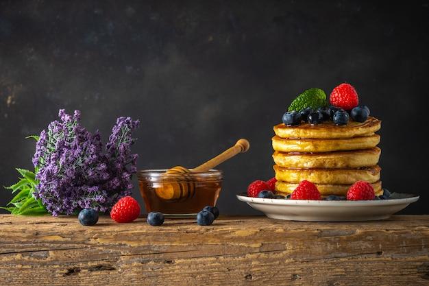 Deliciosas panquecas com frutas frescas na mesa de madeira rústica