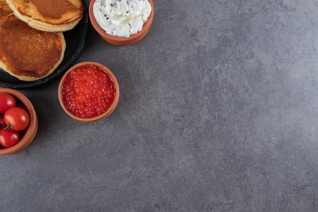 Deliciosas panquecas com tomates-cereja vermelhos colocados no fundo de pedra.