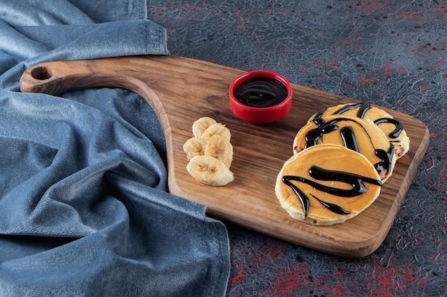 Deliciosas panquecas decoradas com chocolate na placa de madeira com bananas.