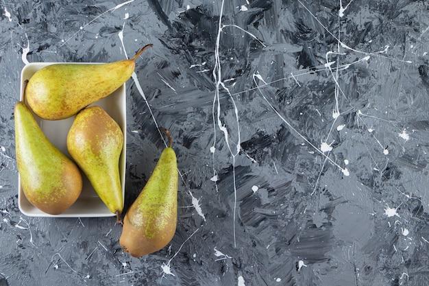 Deliciosas peras maduras frescas colocadas sobre fundo de mármore.