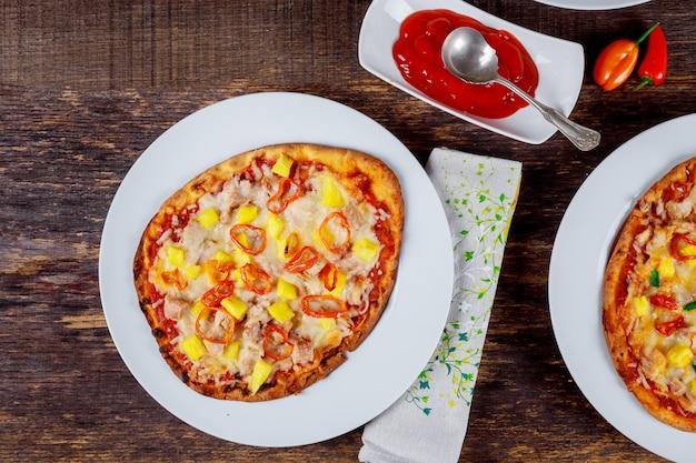 Deliciosas pizzas italianas servidas na mesa de madeira com ingredientes tiro de cima