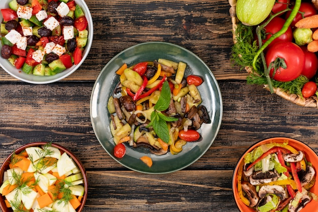Deliciosas saladas de legumes em diferentes tigelas na vista superior de mesa de madeira
