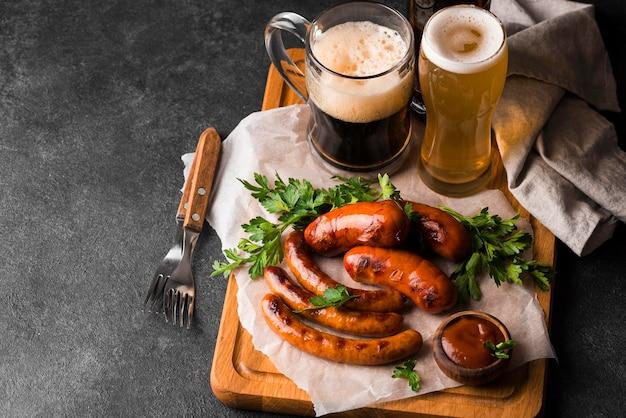 Deliciosas salsichas e cerveja de alto ângulo