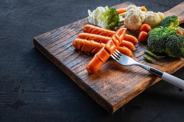 Deliciosas salsichas grelhadas e legumes saudáveis em uma mesa de madeira