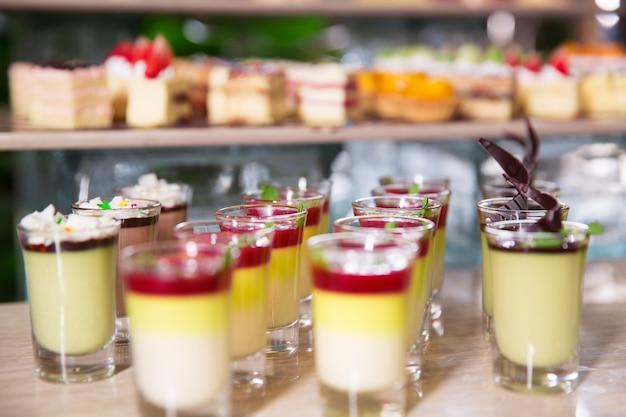 Deliciosas sobremesas em copos de shot na tabela de bufete