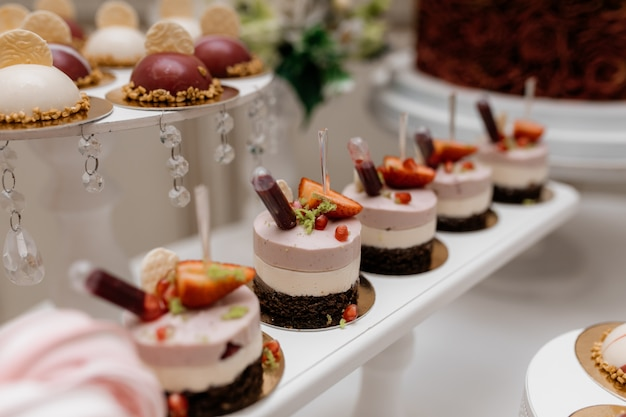Deliciosas sobremesas mousse, decoradas com morangos no bar de doces para banquetes