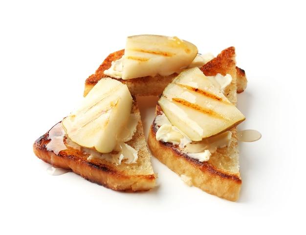 Deliciosas torradas com pêra, manteiga e mel no branco
