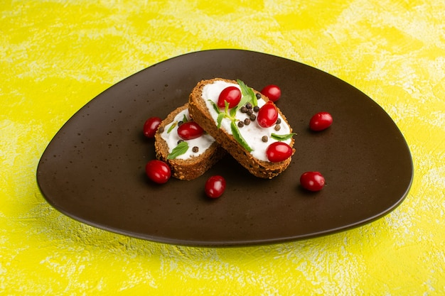 Deliciosas torradas de pão com creme de leite e dogwoods dentro de um prato marrom sobre amarelo