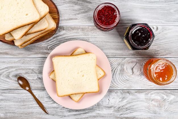 Deliciosas torradas no prato rosa com compotas e colher de madeira na mesa de madeira.