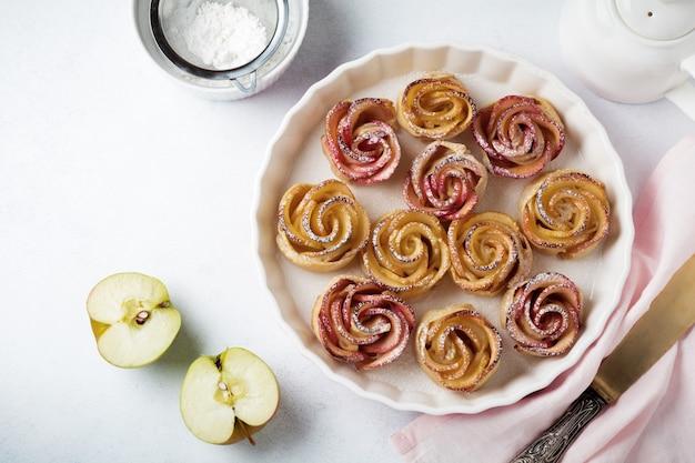 Deliciosas tortas com uma rosa de maçã em forma de cerâmica em uma superfície de concreto leve ou pedra