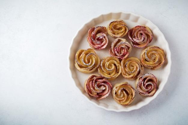 Deliciosas tortas com uma rosa de maçã em forma de cerâmica sobre uma superfície de concreto leve