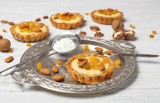 Deliciosas tortas crocantes com amêndoas e passas na mesa de madeira