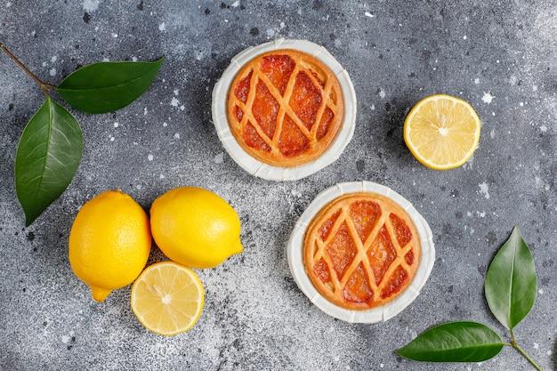 Deliciosas tortas de limão com limões frescos, vista superior