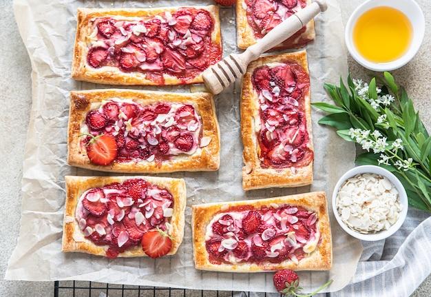 Deliciosas tortas doces fatiadas com morango. mini tartes de massa folhada com morango, requeijão, amêndoa e mel. vista do topo. fundo de concreto claro.