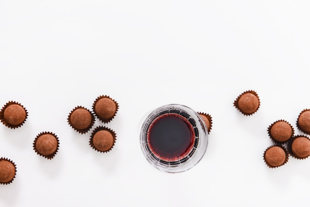 Deliciosas trufas de chocolate e vinho tinto na superfície branca