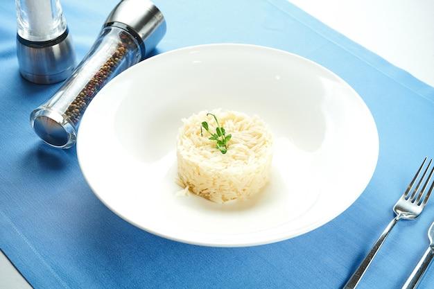 Delicioso acompanhamento para os pratos principais - arroz cozido com microgreen em um prato branco sobre uma toalha de mesa azul. vista de perto