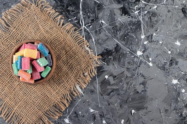 Delicioso alcaçuz em uma tigela de madeira colocada sobre a mesa de mármore.