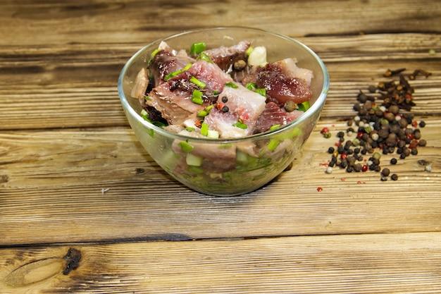 Delicioso arenque salgado com especiarias em uma tigela de vidro na mesa de madeira