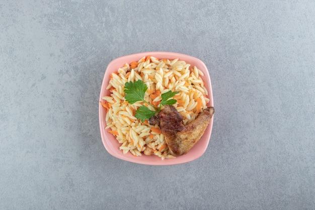 Delicioso arroz com asa grelhada em uma tigela rosa.